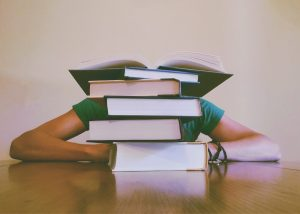 child sitting at desk behind stack of books
