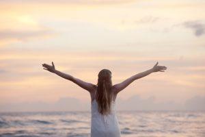 woman arms spread sunrise beach